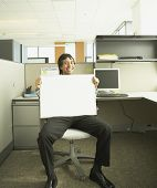 Hispanic businessman holding a blank dry erase board in his lap