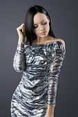 Sensual Brunette With Fashion Silver Dress With Hand Near The Face