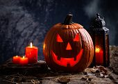 Glowing Jack-o-lantern With Burning Candles And Lantern On A Wooden Surface And Dark Background poster