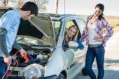 Hombre de cables de arranque ayudan a reparar dos amigas del coche