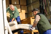 pic of movers  - Two male movers putting furniture and boxes  in moving truck - JPG