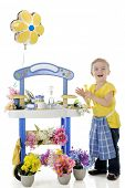 An adorable preschooler delighted as she tends her flower stand.  The stand's signs are left blank for your text.  On a white background.