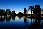 Orlando downtown skyline panorama silhouette over Lake Eola at dusk with urban skyscrapers.
