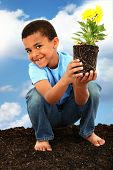 image of missing teeth  - Adorable  Black Boy Child Planting Flowers for Earth Day Barefoot in Soil Holding Flower - JPG