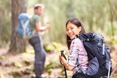 Hikers. Couple hiking in forest. Woman hiker smiling happy at camera walking with hiking poles. Youn