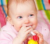 Cute little baby girl playing with teething toy