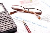 Blank application for life insurance with fountain pen, calculator and glasses. Other documents like
