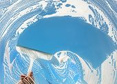 Window cleaner using a squeegee to wash a window with clear blue sky poster