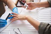 Manicurist Filing Lady Fingernails While She Holding Shiny Nail Polish Bottle poster