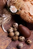 stock photo of pasqua  - Easter still life with quail eggs chocolate egg and Easter dove on wood table - JPG