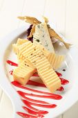 Two sorts of hard cheese on a plate decorated with jam and sallow thorn