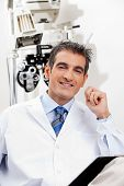 Portrait of a happy optometrist smiling while sitting in his office