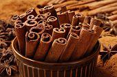 Cinnamon sticks in brown ceramic ramekin with ground cinnamon and star anise in background.  Macro with shallow dof.