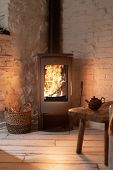 Vertical Photo Of Wood Stove Fireplace With Fire In Metal Body And Glass Door. Wicker Basket In Comf poster