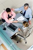 picture of business-partner  - Image of business partners handshaking at meeting while friendly man sitting near by - JPG