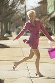 Businesswoman running  on sidewalk