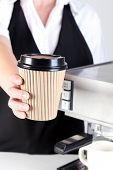 Photo of a Barista handing you a coffee in a disposable paper takeaway cup.