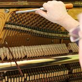 Old german piano during a tuning. Unrecognizable master.