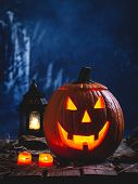 Glowing Jack-o-lantern With Burning Candles And Lantern  On A Dark Spooky Background poster