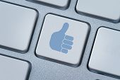 image of follow-up  - Thumbs up or like symbol at the computer keyboard - JPG