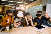 Five Young Funny People Sitting At The Table In Front Of Each Other, Using Virtual Reality Goggles,  poster