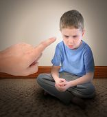stock photo of discipline  - A sad little boy is getting a time out with a finger pointing at the child for a discipline parenting concept - JPG