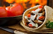 stock photo of flat-bread  - A spicy gyro donair with tomatoes and parsley against a hardwood fire background - JPG