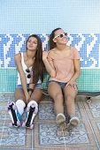stock photo of roller-derby  - Two young skateboarding and roller skating girl friends sitting in empty swimming pool outdoors - JPG