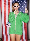 picture of roller-derby  - beautiful young pretty woman in sunglasses with national usa flag in background sucking a lollipop - JPG