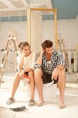 stock photo of bad mood  - Exhausted couple sitting in bad mood in house under construction - JPG