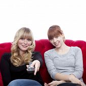 Young Beautiful Blond And Red Haired Girls On Red Sofa In Front Zapping Of White Background