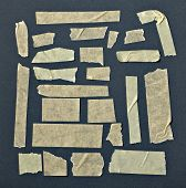 picture of gey  - collection of various adhesive tape pieces on black background - JPG