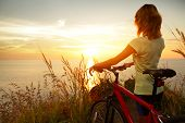 Young lady standing with bicycle on a sea coast and enjoying sunset
