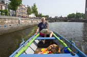 Man with boat and dog in Amersfoort at the Eem river