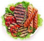 Grilled steak,sausages and vegetables over lettuce leaves.