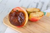 stock photo of rotten  - Rotten apples on wooden board on table - JPG
