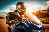 stock photo of biker  - Biker in helmet and leather jacket racing on the road - JPG