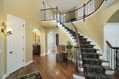 stock photo of entryway  - Foyer in luxury home with curved staircase - JPG