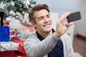 Happy man taking self portrait through smartphone during Christmas at home
