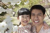 Portrait of smiling father and daughter enjoying the cherry blossoms