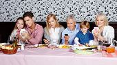 Family looking at their smartphones at the dinner table