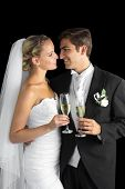 Gorgeous young married couple posing holding champagne glasses on black background