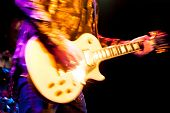 image of guitarists  - motion blur abstract of a glam rock guitarist wearing glitter clothing - JPG