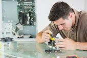 stock photo of hardware  - Handsome serious computer engineer repairing hardware with pliers in bright office - JPG