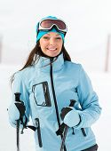 Half-length portrait of female who goes skiing and wears goggles and sports jacket for winter sports