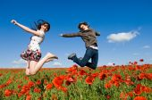 Beautiful Couple Jumping In The Poppy Field