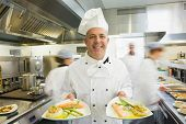 Mature head chef presenting proudly two dinner plates standing in a busy kitchen