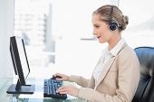 Smiling blonde call center agent working on computer in bright office