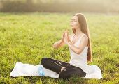 Attractive Woman Practices Yoga In Nature. Lotus Pose, Eyes Closed