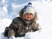 stock photo of ruddy-faced  - Funny little boy playing in snow outdoors in winter - JPG